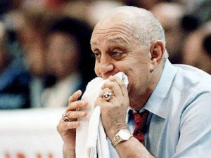 Jerry Tarkanian biting on his trademark towel as he coaches his team.