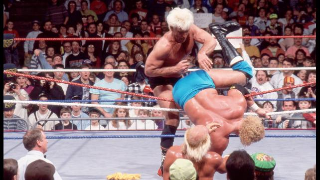 Flair wins the Royal Rumble and the WWF Championship in 1992. Hogan and Flair stand at an arm's length from each other.
